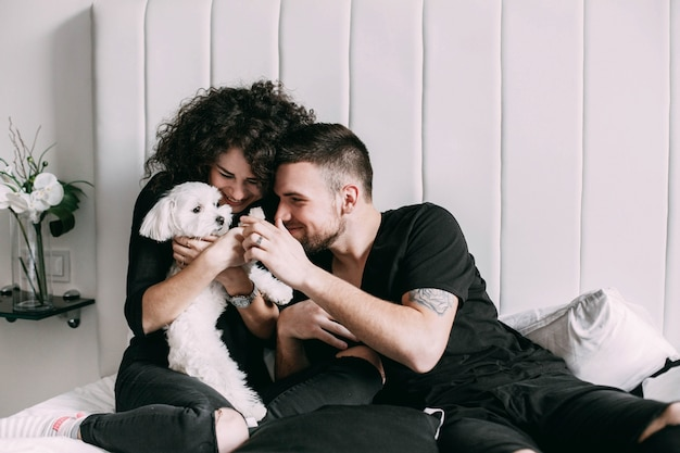 Мужчина и женщина в черном играют с маленькой белой собакой на кровати