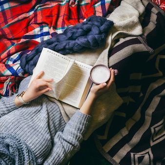 Посмотрите сверху на молодую женщину, пить кофе, когда она читает книгу