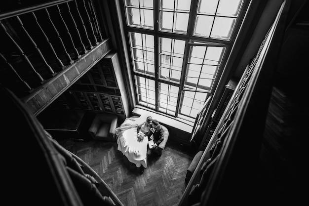 美しい若いカップルは、古い部屋のソファに一緒に座って