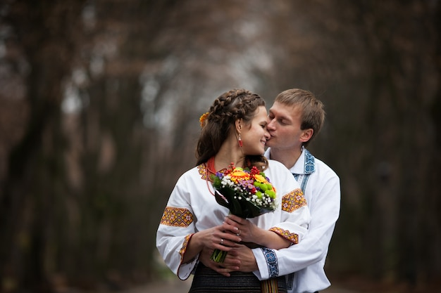 美しいウクライナの花嫁と新郎のネイティブ刺繍は、公園の木の背景に、伝統的な結婚式