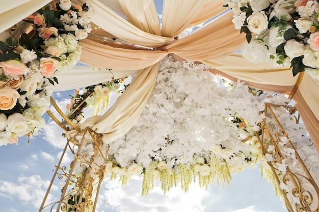 結婚式の祭壇の上部の下に撚られた衣服