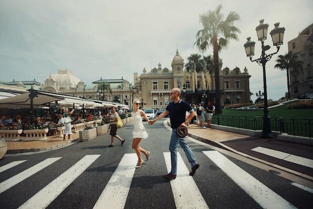 Мужчина и женщина держат друг друга за руки, пересекая улицу в монте-карло