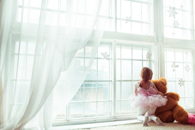 «девочка, обнимающая плюшевого медведя, смотрящего в окно»