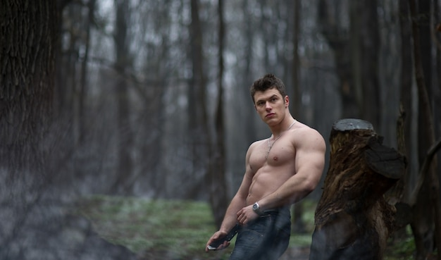 「森の中でポーズをとっている肉薄な男」