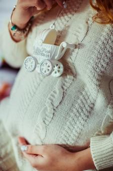 Женщина держит белую игрушечную коляску на ее беременном животе