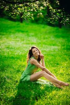 美しい若い女性は緑の庭に座って