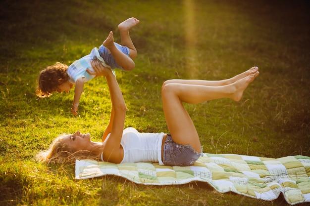 Блондинка мать поднимается в небо ее маленький сын, лежащий на траве