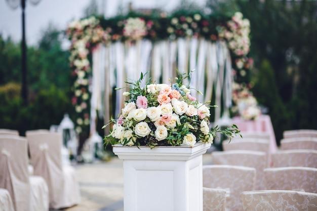 豊かなバラの花束が並んだ列が外に立つ