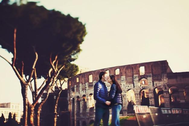 男はコロッセオの前に鼻で女性にキスする