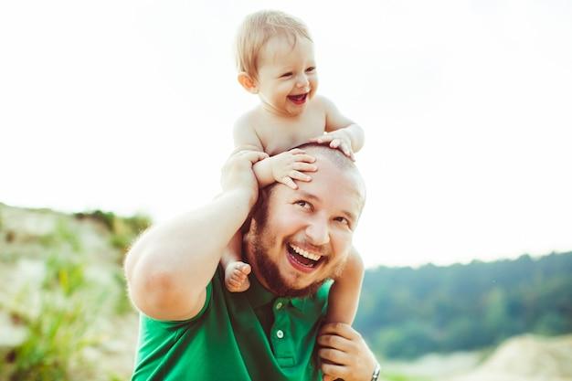 緑のシャツの父親は首に小さい息子を抱えている