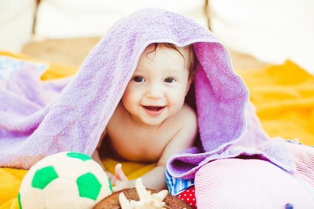 Маленький мальчик лежит под фиолетовым полотенцем