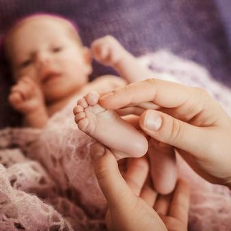 父は優しい赤ちゃんの足に触れる