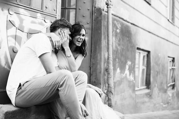 Красивый и молодой мальчик и девочка сидит рядом с дверями