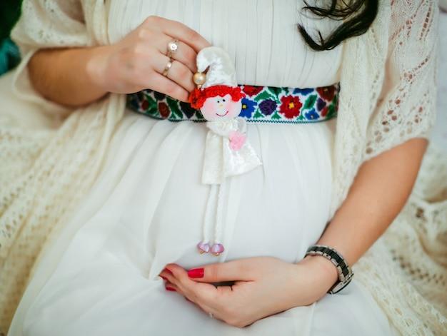 女性は妊娠中の腹に小さなおもちゃを持っています