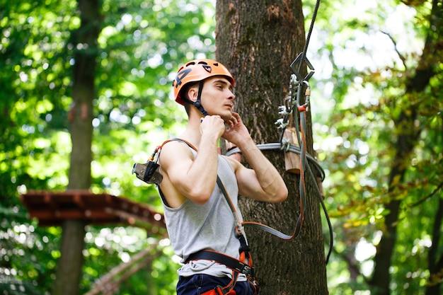 男は公園のロープに登る準備をする