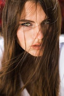 見事な緑色の目の女は、赤い花の前に座っている