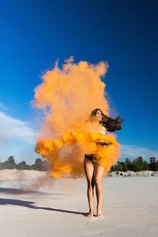 青い空の下に白い砂浜でオレンジ色の煙で女性の踊り