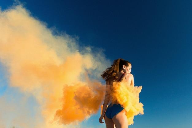 白い砂浜でオレンジ色の煙で青い水泳のスーツの女の子