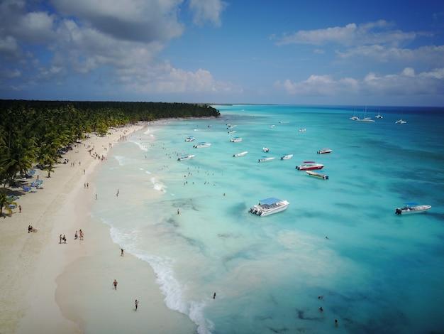 ドミニカ共和国のどこか金色のビーチに沿ってターコイズブルーの水上を見上げてください