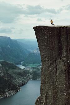 黄色のジャケットを持つ男が岩の上にポーズをとる