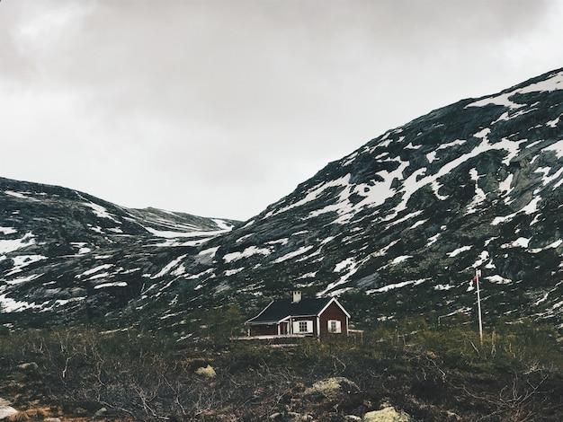 雪で覆われた山の前には孤独なキャビンが立っています