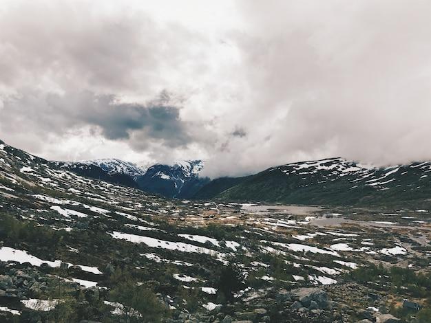 雪で覆われた山々に重い雲がぶら下がっている