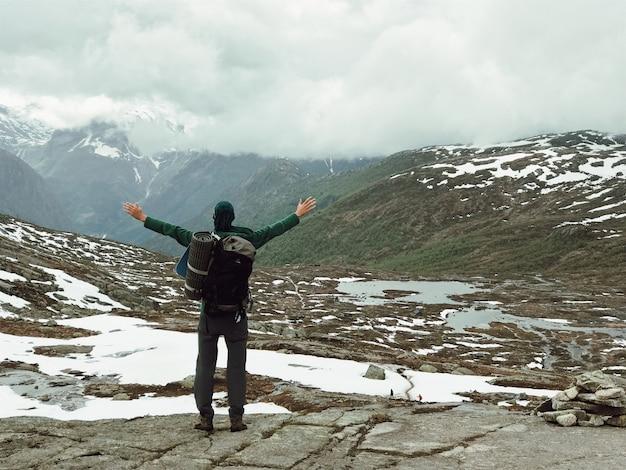 リュックサックを持つ男は豪華な山の景色を賞賛する