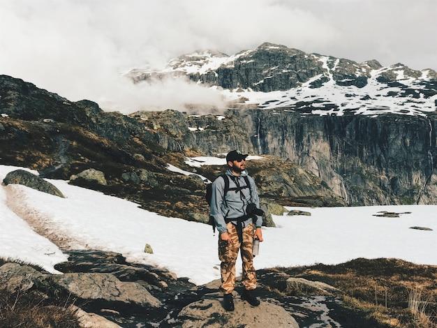 カメラとリュックサックを持つ男は、雪で覆われた山の前に立つ