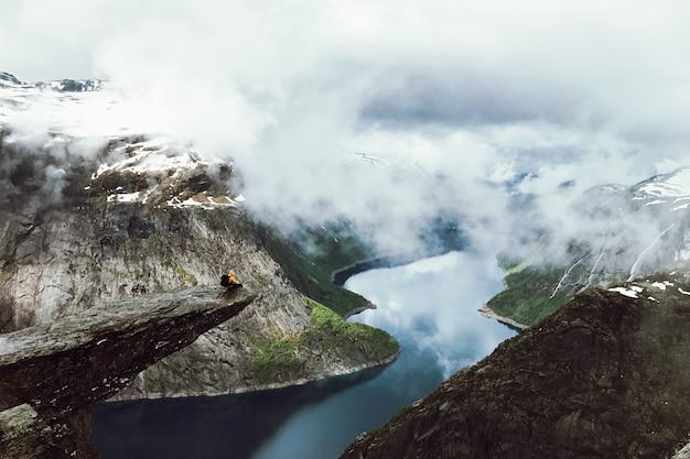 男は山の前でトロルグンガの終わりに座っている