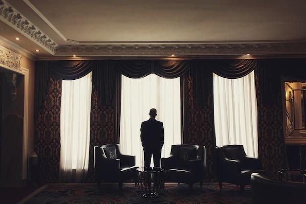 孤独な男は部屋の窓の前に立つ