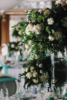 白いバラの花束は、レストランの夕食のテーブルの真ん中に立っています