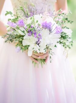 花嫁の腕の中のラベンダーと白いバラの花束