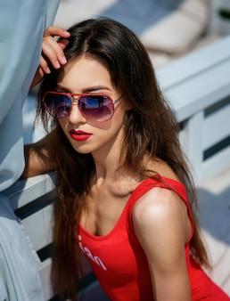 Красивая женщина в красном купальнике сидит на белом диване за пределами