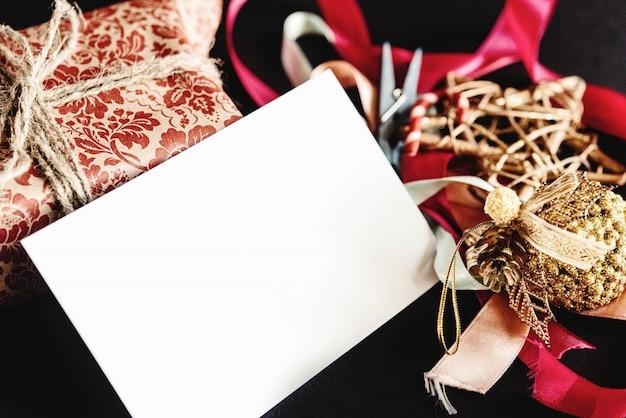 Подарочная упаковка, рождественские украшения и белый конверт