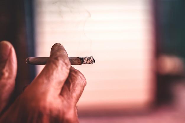手にタバコを持つ男