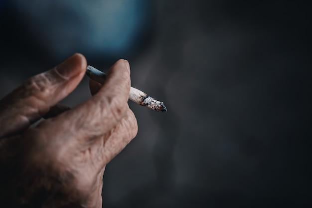 老人の手でタバコを吸う。ニコチン中毒。