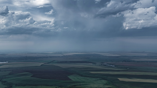 畑と谷を覆う暗い雷雲。嵐の前の瞬間。