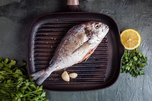 Сырая рыба дорадо со специями и лимоном. вид сверху