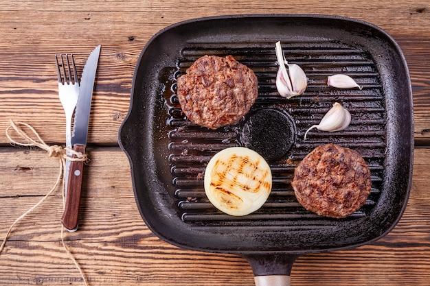 Жареные котлеты из говядины с луком и чесноком на сковороде с вилкой и ножом