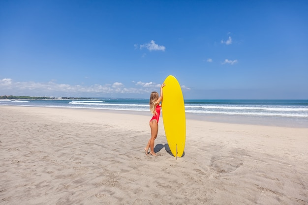 ビーチで一人でサーフボードと赤い水着の長い髪とセクシーな若い女性