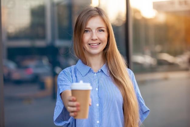 Счастливая молодая женщина улыбается, предлагая кофе в одноразовых бумажных стаканчиков