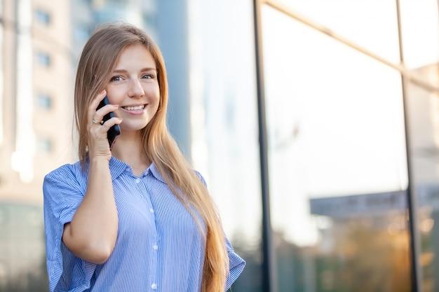 Крупным планом счастливой привлекательной женщиной, говорить на мобильном телефоне напротив офиса