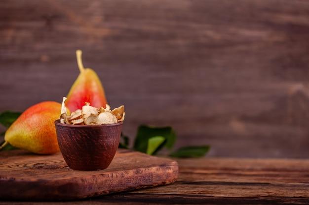 Нарезанные домашние сушеные груши в чашке со свежими грушами на столе, копией пространства