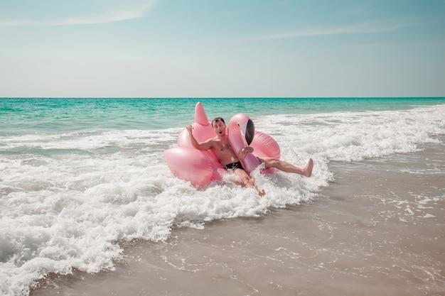 男はピンクのフラミンゴインフレータブルプールフロートで楽しんでいます。