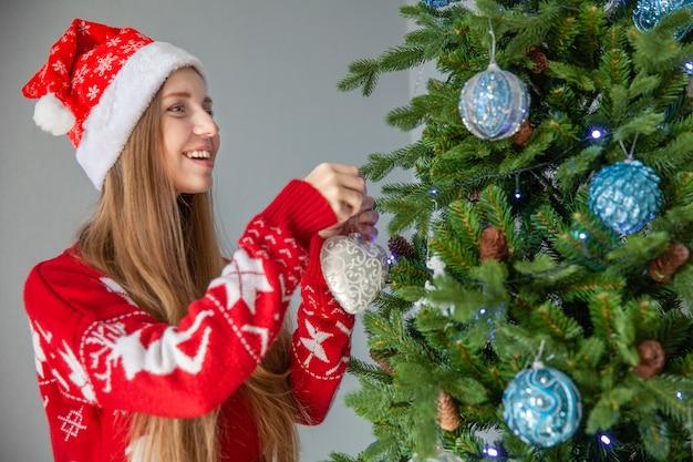 Счастливая женщина в шляпе санта украшают елку,