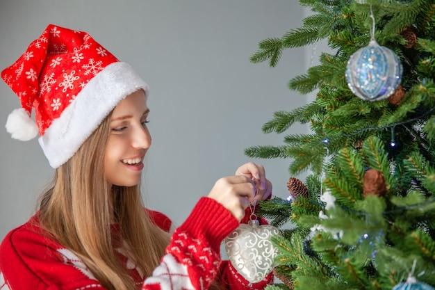 Счастливая улыбающаяся девушка в шапке санта-клауса, украшающая елку сердечными шарами