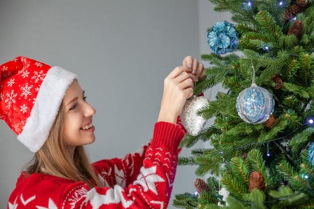 Счастливая молодая женщина в шапке санта-клауса украшения елки с шарами