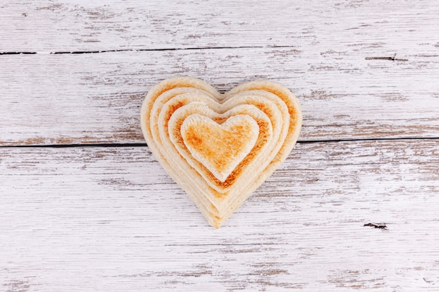 木製テーブルの上のトーストしたパンの心の山、大家族でのサポート