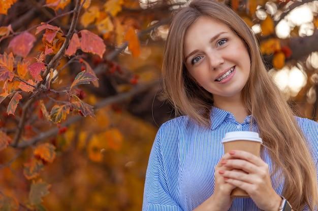 秋の赤い木に行くコーヒーカップと幸せな若い女