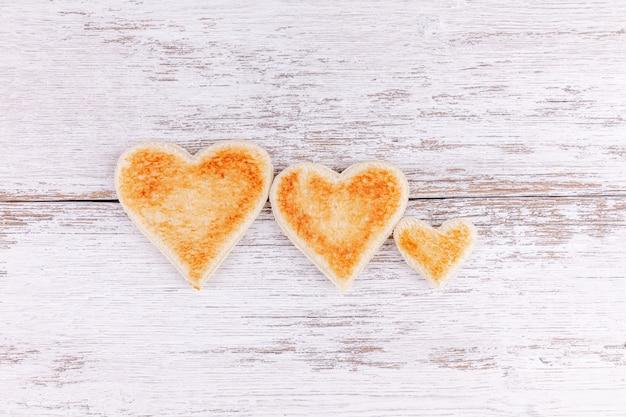 木製のテーブル、幸せな家族で朝食の概念にトーストしたパンの心